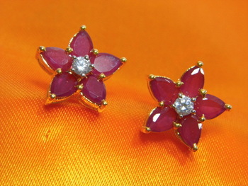 Beautiful Flowery pattern Earrings made of Ruby stones and American Diamond at the centre.