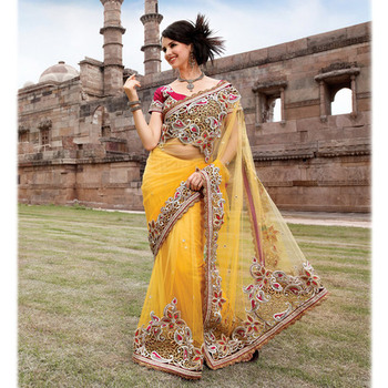 Net fabric party wear saree in yellow color with embroidery and stone work