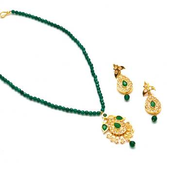 Anvi's uncut stones pendent and earrings with emeralds beads