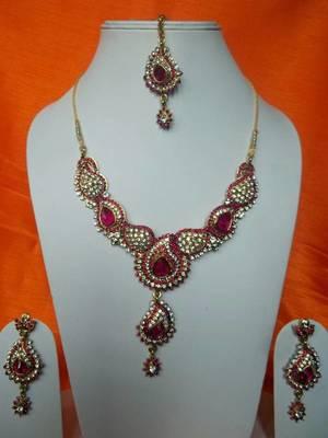 bridal rani pink stone and zircon studded set with matching earrings and maang teeka