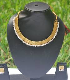 Traditional golden choker necklace set with pearls.