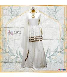 This off white dress has a peplum top with antique handwork done in three layers with a banarasi skirt